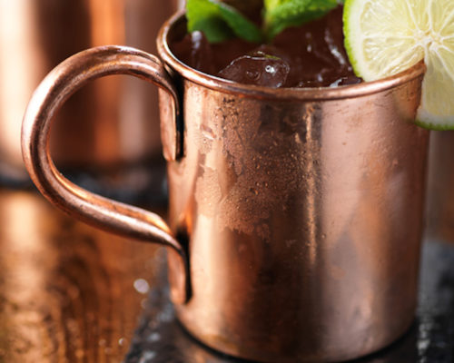 moscow mule cocktail on wooden table close up